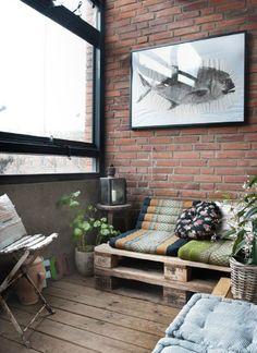 Rustic bohemian enclosed deck. Love the global styling, repurposed crate seating and exposed brick.