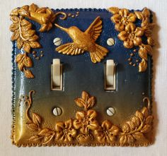 This polymer clay double switch plate was created on a sheet of blue to metallic gold Skinner blend left over from a class. Using the same metallic gold clay all the pieces were molded using PJ011 Hummingbird Lane mold. Dots and tendrils were handmade and added to accent the design. Care was taken to keep the switch areas free of encumbrances.