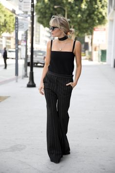 Brooke Testoni wears pin-stripe pants, a black top and skinny scard