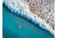 Aerial view of young woman swimming on the pink swim ring by den-belitsky on @creativemarket