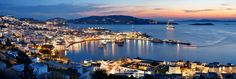 Mykonos Bay, Greece. One of the most classical view of Mykonos at sunset with sparkling lights. The night life starts.   About One Photo a Day: As we publish one fresh phototo a handful of social media platformsdaily for … Read More