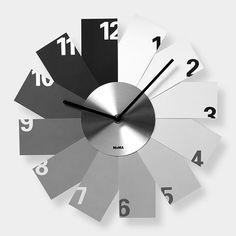 """Monochrome Wall Clock    This clock has a slim body and easy-to-read minimal design. Each """"blade"""" of the Monochrome Wall Clock is a different shade, a progression of light to dark that suggests the passage of morning to night. The hour markers progress from dark to light as time passes. One AA battery and hanging hardware included. $45"""