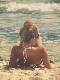 girl sunbathing on the beach // white bikini // sand seaside // on the shore // top bun