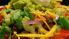 Potato slices form the base for a platter of hearty beef and bean nachos garnished with tomato, lettuce, sour cream, and guacamole.