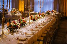 Traditional long tables with deep-colored flowers and gold candelabras.