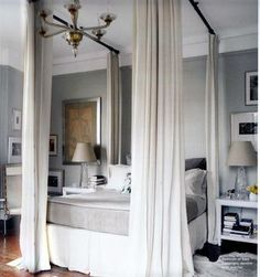 Style editor Dara Caponigro's room as featured in the Domino Book of Decorating. Dara created the look of a traditional four poster canopy bed by mounting drapery rods to the ceiling and attaching drapes at each corner of the bed.  Produced a very modern yet romantic result.