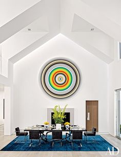 A painting by Gary Lang radiates above the dining area, which is furnished with a bespoke table by Hudson Furniture and a suite of Dax Design chairs.
