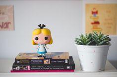 Três edições do livro Alice no País das Maravilhas e a Alice na versão Funko Pop
