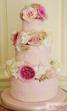 light pink cake with white lace overlay and dark pink and white frosting flowers