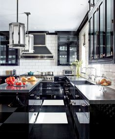 """Delineating the edges of a kitchen by using a strong color on the cabinets and appliances can actually make the room feel more spacious. A lacquered finish gives you a ton of reflection that only enhances the effect."""