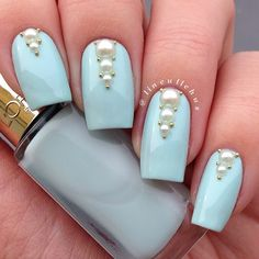 Pale blue polish with graduated sizes of pearls and tiny gold studs #nailart