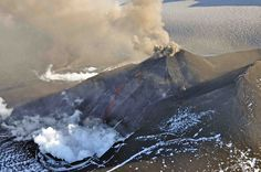Photo of Veniaminof volcano taken by plane on Aug. 18, 2013, in the Aleutian Range in Southwest Alaska. This image shows a steam cloud from lava melting snow and ice and an ash cloud billowing from the summit.