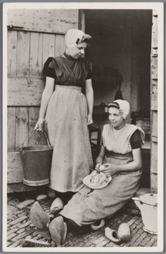 Twee vrouwen in protestantse Zuid-Bevelandse streekdracht. De vrouwen zijn gekleed in daagse dracht of werkdracht. De rechter vrouw is aardappelen aan het schillen. 1905-1946 #Zeeland #ZuidBeveland #protestant