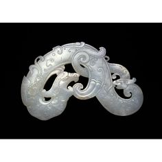 Chime  Date: Qing Dynasty - Early Republic Period. Location: China.  An object carved from white jade of a dragon wrapping around to its tail. The style is from the Warring States period and early Han Dynasty.
