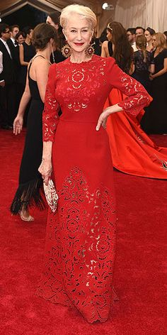 The Most Unbelievable Dresses at the 2015 Met Gala | HELEN MIRREN | in a deep red three-quarter-length sleeved dress, with lace cutout design and oval-shaped, ruby-colored earrings.