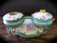 Gerard Dufraisseix & Abbot France Dresser Set. This set is beautifully painted in pink, yellow blue, lavender and sea foam green. There is gold detail on the rims and handles. The seat has: a hair reciever, fowder dish and tray.The jars have three feet on which they stand.