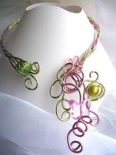 Pomme    Ce collier est réalisé en fil dalu et se pare dun papillon, dune fleur et de perles magiques.  Le tour de cou est travaillé en torsade pour une meilleure solidité.  Couleur : Vert pomme et rose  Un bracelet et une bague peuvent être associés sur demande.