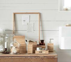 Uma imagem com caixas, doseador de sabonete e copo para escova de dentes, tudo em bambu.