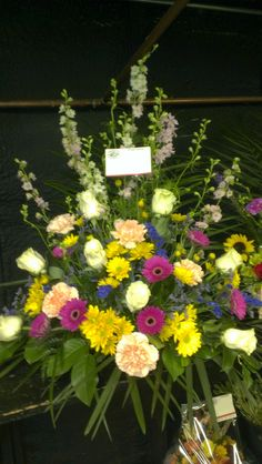 This funeral display arrangement consists of gerbera daisies, carnations, roses and snap dragons. americasflorist.com