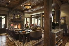 A rustic, open concept living room offers a roaring fire; luxurious leather chairs with nailhead trim; and a rough-hewn, wood mantle.