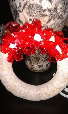 Een rieten krans van de Action , kerst lint van de Xenos plastic lepels van AH  De rode plastic lepels gesmolten boven een kaars verbogen als een kerst ster achtige bloem. De eerste 20 lepels mislukken wel maar daarna lukt het! pff