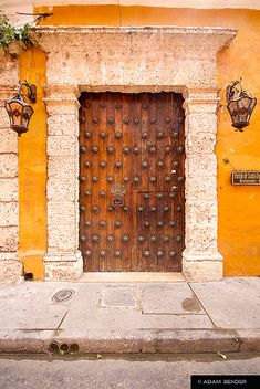 A wooden door with brass stars, at a building in the walled city of Cartagena, Colombia. Nice example of the colonial architecture.