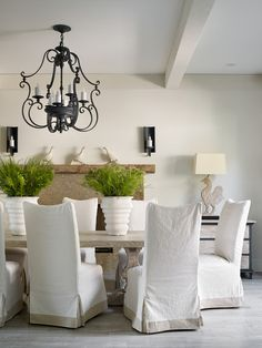 Slipcovers can update a tired dining set. Whether your current set is looking worn out, or you're just ready for a change, why not give slipcovers a try? They're far less expensive than springing for a whole new set of chairs and can completely alter the look of your dining room. If you want to give wooden dining chairs an upholstered look and feel beneath the covers, have custom slipcovers made and ask for a padded lining for comfort. Transitional Dining Room by Beth Webb Interiors