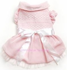 SKU: Pink Smocked Sweater Dress  by Oscar Newman  This pretty machine-smocked dress in soft, bubblegum pink is the classic girly dress for every special occasion. It features hand-sewn pearls, a sateen bow, and a dainty tulle ruffle peeking below the hem. Pop-sleeves add to this girlish charm of this quintessential dress.  Price: $67.00