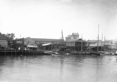 A view of the river frontage of the Harris boatyard taken from the Wivenhoe side of the River Colne. - National Maritime Museum