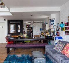 Com jeitinho de loft, este apartamento abusa dos móveis e acessórios coloridos e dos arranjos de parede descontraídos