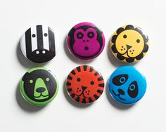 Set of six metal pin back badges / button badges / flairs.    Each badge shows a different wild animal design: a lion, tiger, monkey, panda, zebra,