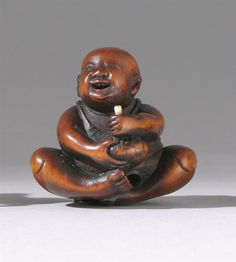 """WOOD NETSUKE Mid-19th Century Depicting a karako holding a candle and a piece of fruit. Height 1.25"""" (3.2 cm)."""