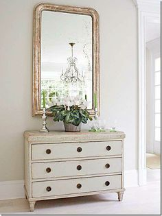 Love this mirror hung over a pretty, neutral chest with the two candlesticks and flower as balance.