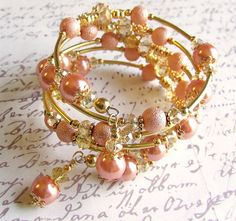 Beaded Memory wire Bracelet - Peach Shimmer - By White Raven Designs           Created in Gold tone metals and features lovely peach glass based pearls, Golden topaz glass crystal for a touch of sparkle, Gold flower beads, Filigree bead caps and finshed with two beaded dangles.