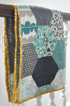 Hexagon quilt with contrasting binding and hand stitching