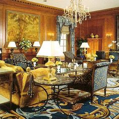 Blue and gold Savonnerie rug, gold sofa, blue chair, wood paneled walls, crystal chandelier. Picture of Elegance Blog: Classic Style
