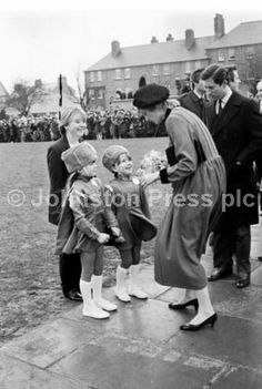 Princess Diana and Prince Charles meet two little majorettes when they visit Craigroyston in Edinburgh, March 1983. Princess Diana accepts a posy of snowdrops