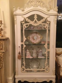single door display cabinet with figurines and antique Limoges and Shelley china