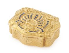 A Continental gold and sapphire snuff boxof cartouche shape in mid-18th century style, the cover embossed with dragons and cornucopiae and centered by graduated sapphires in a shell arrangement, sides chased with foliage and strapwork, the base engraved en suite, late 19th century. -- Sotheby's