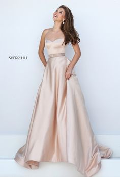 This satin ballgown features and illusion neckline, beaded belt, and pockets…
