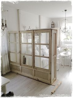 Salvaged Window Room Divider - this showcase was built from salvaged windows and is used to divide a large area into rooms.  This is a clever concept that doesn't block the light or close off the space - Bianca Planner
