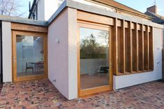 The additions include a rear and a side extension and these are tied into the renovated existing garage to read as a single form externally that wraps around the original house. The external walls of the extension are finished in a pale pink, textured render relating to but also consciously different to the finish on the existing house.