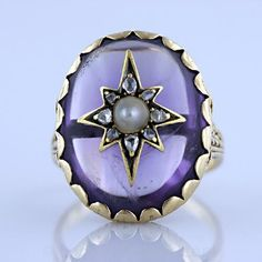This ring highlights a 17.50 carat oval shaped cabochon amethyst set in a scalloped collet and adorned with a star appliqué of pearl and rose cut diamonds in gold, so fashionable for its time.  It is crafted in 14 karat gold with an expertly engraved gallery and shoulders. The ring is American, circa 1860's.