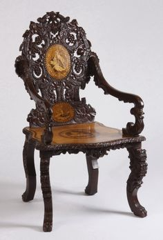 Late century Black Forest pierce carved and inlaid walnut armchair, the backrest with two roundels featuring mou.