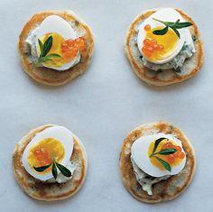 Bite-size blini are topped with a dollop of rich creme fraiche, diminutive quail eggs, and brilliant trout roe.