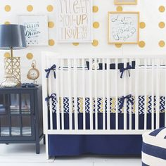 Beautiful nursery features mustard yellow polka dot walls lined with a white crib dressed in chevron bedding and a navy blue crib skirt flanked by a navy and white striped pouf near a dark navy nightstand topped with a gold arabesque lamp. Navy Crib Bedding, Baby Crib Bedding Sets, Nursery Bedding, Baby Cribs, Chevron Bedding, Crib Sheets, Yellow Bedding, Mustard Bedding, Gold Bedding