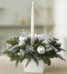 White decorative box filled with Christmas trees filling decorated with white and silver ornaments and a long white taper candle