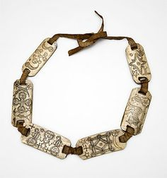 Indonesia ~ North Sumatra | String of amulets from the Toba Batak or Karo Batak people | 19th/early 20th century | Bone and cotton | This string of amulets inscribed with symbols and magic inscriptions is typical of the protective charms worn by priests when undertaking dangerous sorcery.
