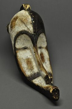 Africa | Large curved, carved wood Fang mask with white pigment and traces of blue and brass tacks. Gabon.