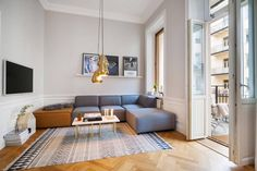 modulares Sofa in Grau, Parkettboden und gemusterter Teppich in Schwarz-Weiß